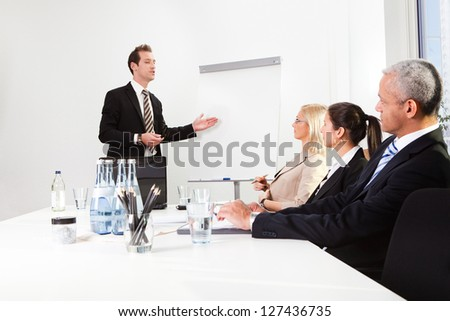 Businessman giving a presentation to his colleagues - stock photo