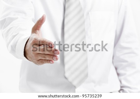 Businessman giving an hand for handshake to seal the deal - stock photo