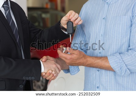 Businessman giving car key while shaking a customer hand at new car showroom - stock photo
