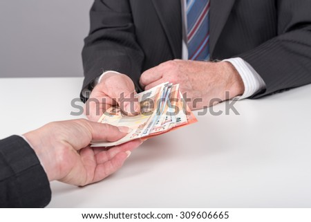 Businessman giving cash money to a person - stock photo
