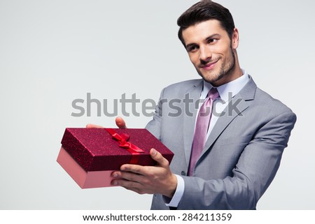 Businessman giving gift box to something over gray background - stock photo