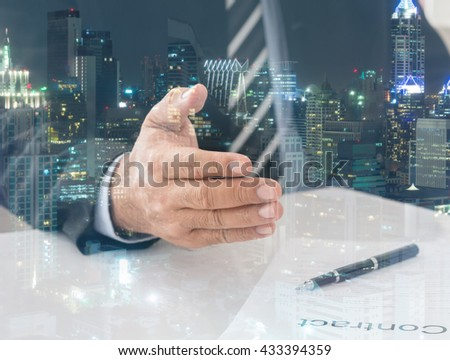 Businessman giving him hand for handshake to partner with city background.  Concept of Business Agreement, Congratulate Mergers.   - stock photo