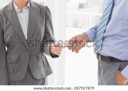 Businessman giving his business card to his colleague in an office