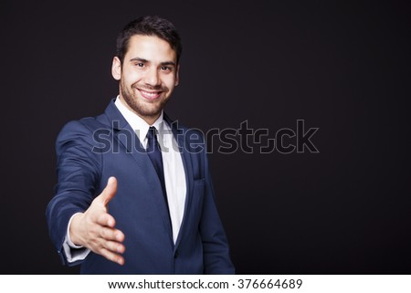 Businessman giving his hand for handshake on black background - stock photo