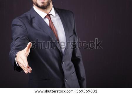 Businessman giving his hand for handshake on dark background - stock photo