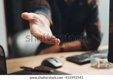 Businessman giving his hand for handshake to his friend - closeup shot - stock photo