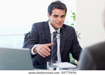 Businessman giving his hand in his office - stock photo