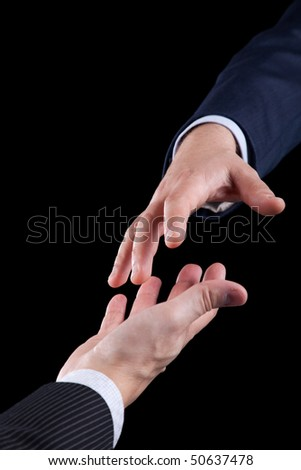 Businessman giving his hand to help another men (isolated on black)