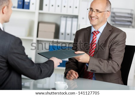 Businessman giving his job application to the employer inside the office - stock photo