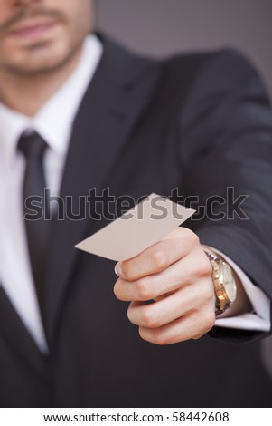 businessman giving his visit card on grey background - focus on hand - stock photo
