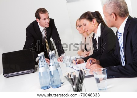 Businessman giving instructiong to his team - stock photo