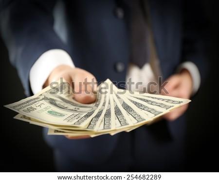 Businessman giving money on dark background - stock photo