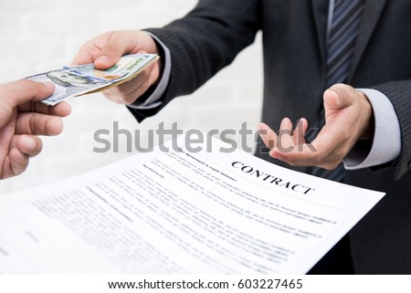 Businessman giving money together with contract - debt, loan and bribery concepts