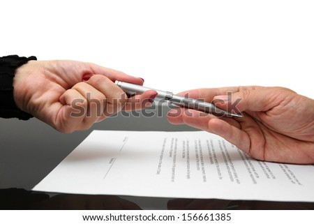 businessman giving pen to businesswoman for signing contract or document - stock photo