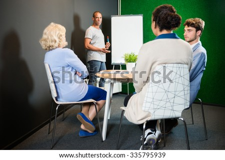 Businessman giving presentation to colleagues in modern office lobby - stock photo