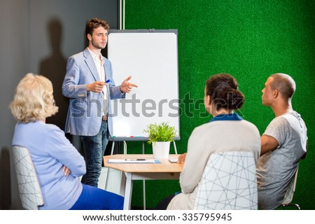 Businessman giving presentation to colleagues in office lobby - stock photo