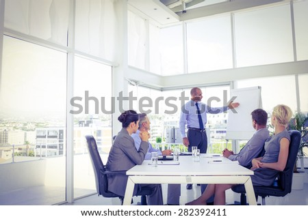 Businessman giving presentation to his colleagues in the office - stock photo