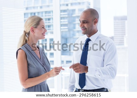 Businessman giving small paper sheet to his colleague in the office - stock photo