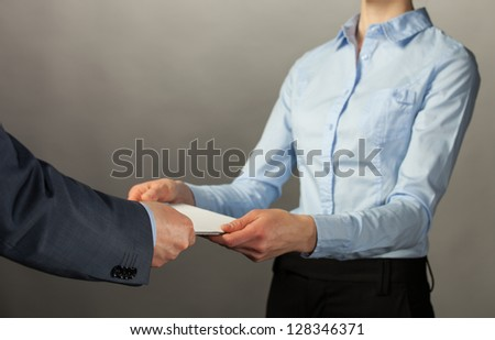 Businessman giving some documents to his secretary, grey background