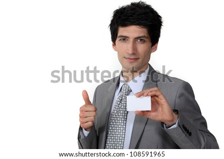 Businessman giving the thumb's up and holding a business card - stock photo
