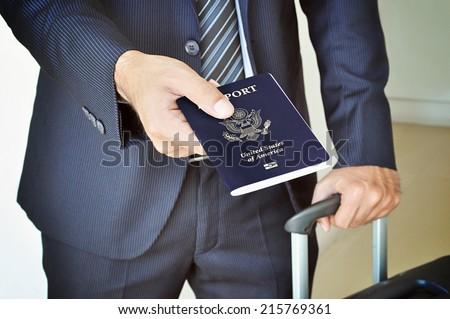 Businessman giving U.S. passport - stock photo
