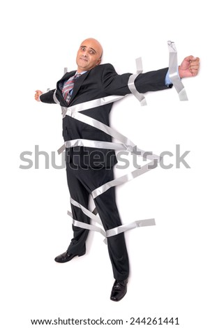 Businessman glued to the wall with duct tape - stock photo