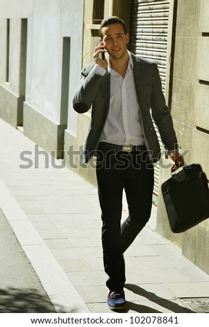 Businessman goes and calls on mobile in city street - stock photo