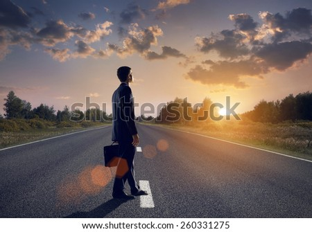 Businessman goes straight on his way on asphalt road - stock photo