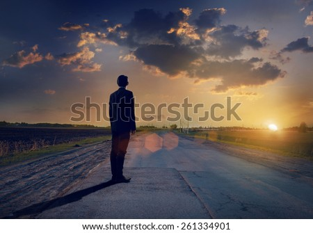 Businessman goes straight on his way on asphalt road - stock photo