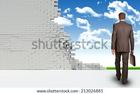 Businessman goes through ruined brick wall - stock photo