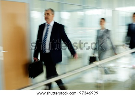 Businessman going along corridor with walking people on background