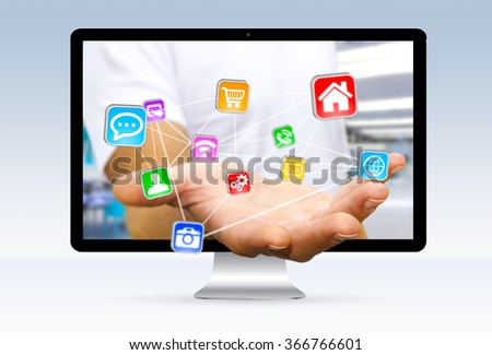 Businessman going out of a computer screen holding application icons interface in his hand - stock photo