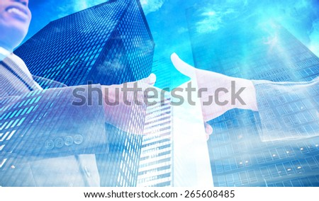 Businessman going shaking a hand against low angle view of skyscrapers - stock photo
