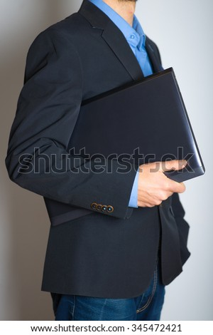 Businessman going to work with a laptop, without a face. advertising or business concept, isolated on a gray background.