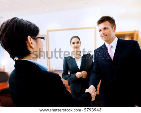 Businessman greeting partner in the meeting room. Selective focus is placed on the hands. - stock photo