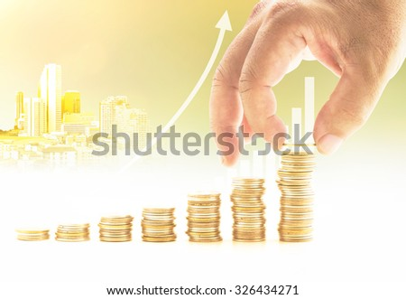 Businessman hand adding golden coin on stacks of coins over graph finance and the city over blurred sunset background. Growth concept. Investment concept. - stock photo