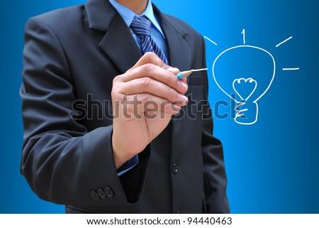 businessman hand drawing a light bulb - stock photo