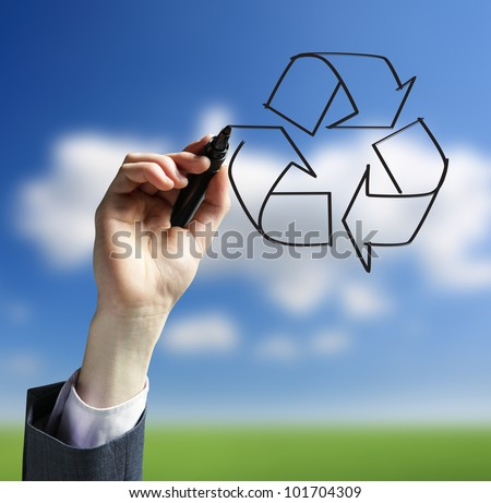 Businessman hand drawing a recycling logo - stock photo