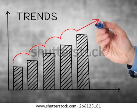 Businessman hand drawing growth trends chart isolated on grey background. Stock Image