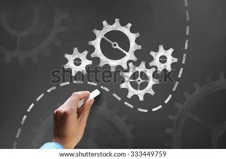 Businessman hand drawing with chalk gears mechanism as teamwork concept