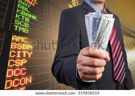 Businessman hand gripping money, US dollar (USD) bills - investment, business concepts