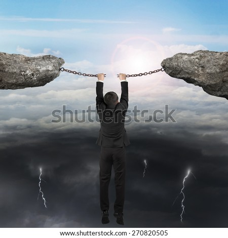 Businessman hand hanging on the cracking rusty iron chains connect two cliffs with opposite weather conditions sky background, bright sun cloudscape and dark cloudy lightning. - stock photo