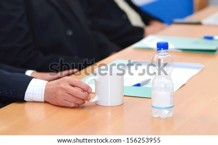 Businessman hand hold a cup on the table - stock photo