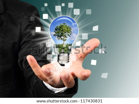 businessman hand holding a blub with tree inside - stock photo