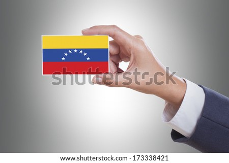 Businessman hand holding a business card with Venezuela flag and clipping path - stock photo