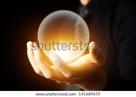 Businessman hand holding a Crystal Ball - stock photo