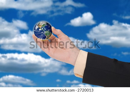 businessman hand holding a globe with a cloudy sky in the background - stock photo