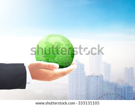 Businessman hand holding a green earth globe of grass on blur abstract sunset background. Go Green, Ecological city, Investment, Ecology, Environment, Corporate Social Responsibility (CSR) concept. - stock photo
