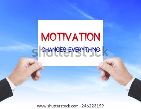 Businessman hand holding a handwritten text for MOTIVATION CHANGES EVERYTHING over blue sky background. - stock photo