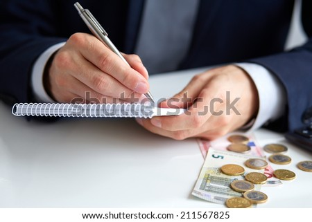 Businessman hand holding a pen writing on notepad with coins & calculator aside - stock photo
